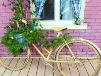Žlutý sázecí stroj na kolo - hnědé městské kolo s květinami poblíž budovy červených cihel během dne.