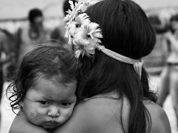 Guarani baby girl on mom's cuddle - grayscale photo of woman carrying baby.
