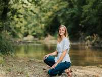 Senior girl in river - woman in white and black floral shirt and blue denim jeans sitting on ground near river.