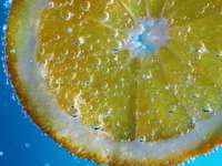close up photo of lemon fruit - Orange in sparkling water, on a blue gradient.