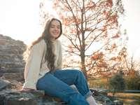 Mädchen, das auf einem Felsen in der Morgensonne sitzt. - Frau im weißen Langarmhemd und in den blauen Jeans, die auf Felsen sitzen. Ohio, USA