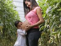 The mom and son - pregnant woman and child standing outdoor.