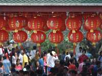 Red for Chinese New Year - hanging round red lanterns near crowd at daytime. Saraburi, Thailand