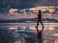 Passeggiata al tramonto - donna che cammina lungo la riva del mare. Cannon Beach, OR, USA