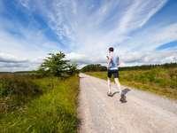Trail running - om alergând pe drum lângă câmpul de iarbă.