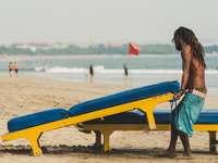 uomo che porta sedia a sdraio - Un uomo che lavora sulla spiaggia di Seminyak. Spiaggia di Seminyak, Indonesia