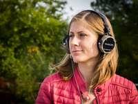 Жена, слушаща музиката през слушалки на открито - снимка с плитък фокус на жена, използваща слушалки с че
