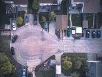 clădire din beton maro și alb - Încercând ceva nou! Fotografiere aeriană a unui sens giratoriu cu mașini într-un cartier suburb