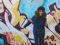 Kvinna som ler framför graffiti - kvinna som bär stickad mössa och svänger armarna. Nashville, USA