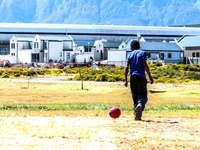 Menino solitário jogando bola. - fekete kabátot és piros nadrágot tartó piros labdát tartó férfi. Dél-Afrika