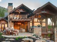 Grande cabane en rondins avec une grande terrasse