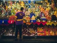 man standing in front of produce stand - Market place in São Paulo , called Mercadão de São Paulo. Mercado Municipal, Brazil
