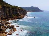 Strandklippe mit Blick auf das blaue Meer tagsüber