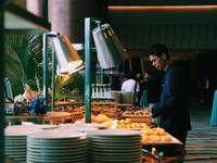 człowiek wybiera jedzenie przy stole w formie bufetu - Mężczyzna obserwuje jedzenie.