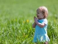 Kleinkind mit blaugrünem Kleid auf grünem Rasen während des Tages