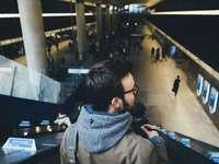 osoba stojąca na schodach ruchomych na stacji metra - Brodaty mężczyzna na schodach ruchomych. Canary Wharf, Londyn, Wielka Brytania