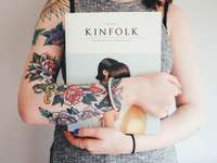 person holding Kinfolk book - Woman with tattoos. Southampton, United Kingdom
