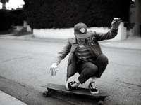 фотография в сивата скала на човек, каращ се на лонгборд
