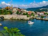 fehér csónak a tenger közelében a városi épületek kék ég alatt - fehér hajó a tenger közelében a város épületei kék ég alatt nappali. . Amasra, Bartın, Tü