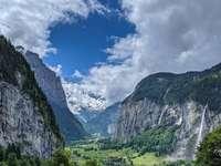 зелени и черни планини под бяло небе през деня