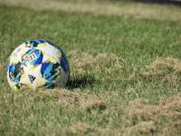 blå vit och röd fotboll på grönt gräsplan - blå vit och röd fotboll på grönt gräsplan under dagtid. Fotboll i gräs.