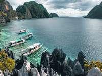 бяла и синя лодка на море в близост до зелена планина
