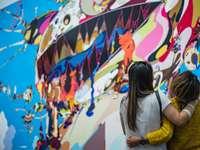 dvě ženy hledí před nástěnnou malbou