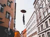 жена, обесена на тел, докато държи чадър