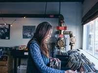 жена, стояща на стерео стелаж с ръкав, държаща ръкав