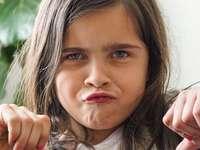 garota em camisa branca de gola redonda - Muito jovem, fazendo uma careta de desaprovação, enquanto dá o polegar para baixo sobre não volt