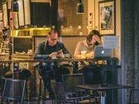 mężczyzna trzyma smartfon siedzący obok kobiety z przodu - mężczyzna trzyma smartfon siedzący obok kobiety przed srebrnym MacBookiem w restauracji. historie
