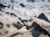 Flygfoto över berg täckta med moln - Toppar. Gran Paradiso, Italien