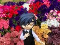 Mitsu framför en blomsterrabatt - Mitsu poserar elegant framför vackra blommor