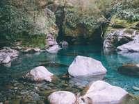 corp de apă între stâncile cenușii și mușchiul verde - corp de apă între roci gri și mușchi verde în timpul zilei. . Noua Zeelanda