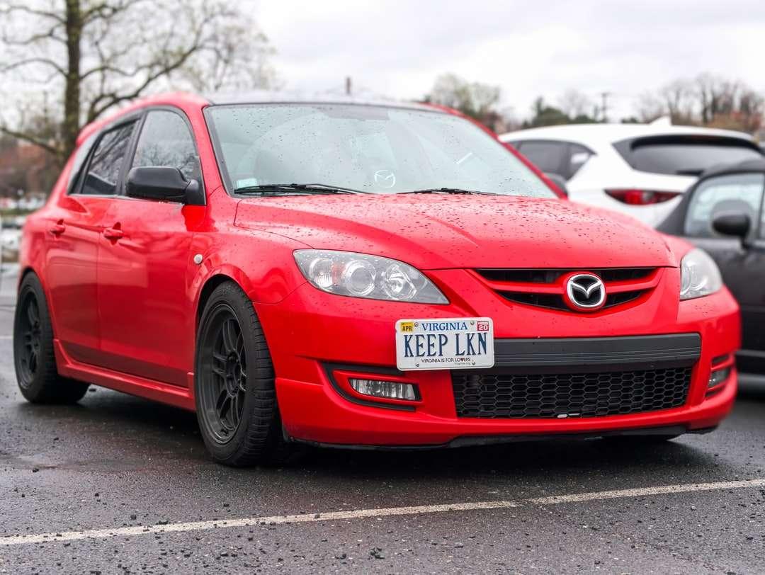 röd bmw m 3 på väg under dagtid - Röd Mazdaspeed3 med en egen registreringsskylt, parkerad på en återförsäljare i Fairfax strax efter regnet (11×9)
