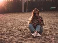 kvinna i jeans i blå jeans som sitter på brun sand - kvinna i blå jeansjacka som sitter på brun sand under dagtid. . Україна, Україна