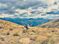 kvinna i vit t-shirt som gör yoga på kullen - Någonstans i Nya Zeeland.