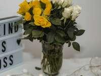 gele bloemen in helderglazen vaas op witte sneeuw - Witte en gele rozen.