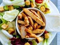 skivad kött- och grönsaksallad på den vita keramiska plattan - Kyckling Caesarsallad, sallad, gröna. Malta