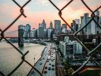 grå betongbyggnad nära vattenkroppen - grå betongbyggnad nära vattenkropp under grå och vit himmel. XX. Rutnät. NYC. New York, USA