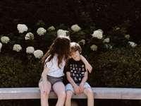 Dos niñas y niños pequeños sentados en un banco de hormigón - dos niñas y niños pequeños sentados en un banco de hormigón cerca del aire libre durante el día