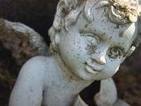 ángel estatua de hormigón - Ángel querubín de hormigón con alas cubiertas de musgo y suciedad en un cementerio o cementerio e