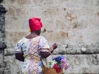 kvinna i vitblå och röd blommig långärmad skjorta - kvinna i vitblå och röd blommig långärmad skjorta som rymmer rosa blombukett. . Havanna, Küba