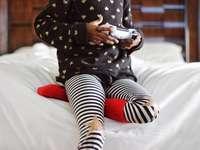 bambini che tengono controller di gioco grigio seduto sul letto bianco - I miei mini giochi sulla tua PS4. Palm Springs, Stati Uniti