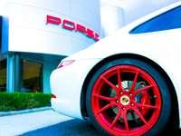 carro branco com roda vermelha - Um Porsche branco com rodas vermelhas e pinça de freio estacionado em frente a uma concessionária