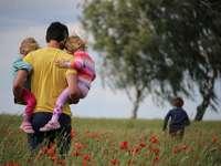 мъж, носещ на момичета на полето от червено оцветено цвете - Насочване към дома преди бурята. Мекленбург-Предна Пом