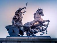dos hombres montando carro estatua