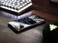 detailní fotografie zapnutý smartphone poblíž klávesnice