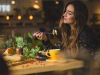 жена държи вилица пред масата