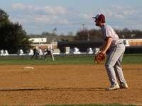 férfi piros baseball mezben és fehér nadrágban